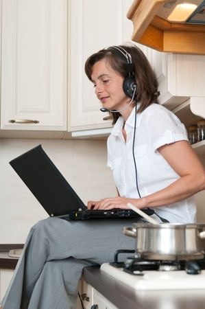 home working: Young business woman working from home on laptop while cooking meal in kitchen