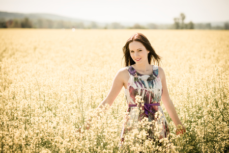 young woman smiling: Young beautiful woman enjoying life in rapeseed field - warm tone Stock Photo
