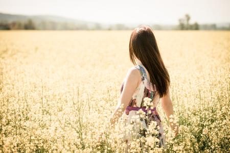 woman in field: Young beautiful woman enjoying life in rapeseed field - warm tone Stock Photo