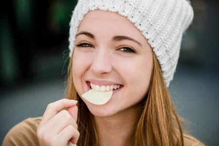Teenager girl in cap eating chips outdoor in street