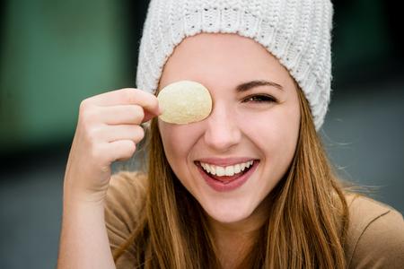 Teenager girl in cap having fun with potato chips on eyes outdoor in street Standard-Bild