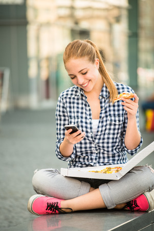 woman eat: Teenager eating pizza in street and browsing internet on phone