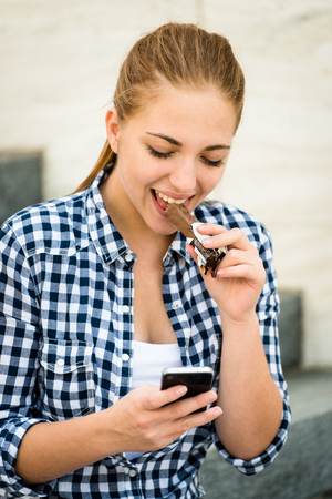 snack bar: Teenager - young woman eating chocolate in street and looking in phone
