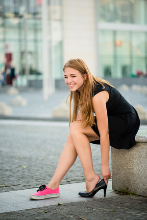 women legs: Changing shoes - teenager puts on high heels instead of sneakers on street