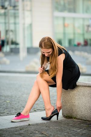 Młoda kobieta zmienia buty na wysokich obcasach ulicy zamiast adidasów