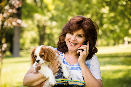 Mature woman calling phone while holding her dog by outdoor in nature Reklamní fotografie