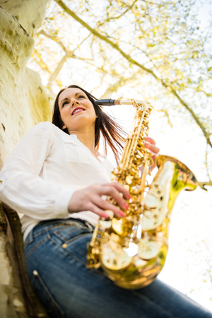saxophonist: Young beautiful saxophonist with saxophone - outdoor in nature Stock Photo