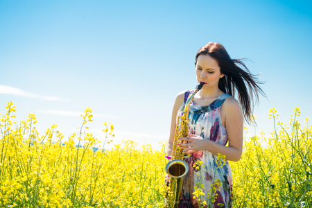 saxophonist: Young  saxophonist playing saxophone in yellow rapeseed field