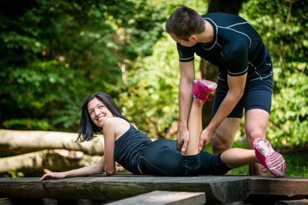 Relax after sport - man massaging calf of his friend outdoor - woman lies on bench