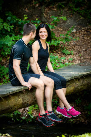 bridge in nature: Young sport couple relaxing after sport training on foot bridge in nature