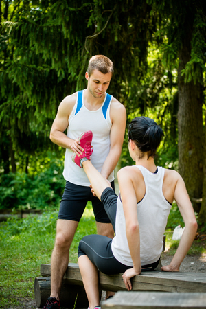 muscle spasm: Man stretches womans leg - muscle spasm after sport training