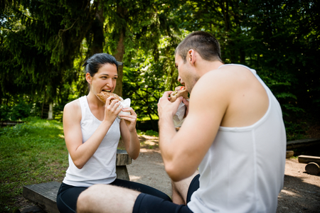 woman eat: Young couple eating together after jogging outdoor in nature
