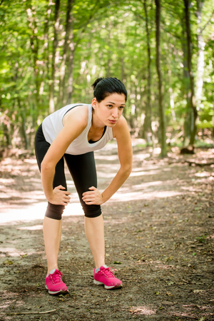 gasping: Tired young woman resting after jogging in nature Stock Photo