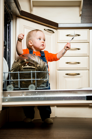 unload: Cute baby helping mother unload dishwasher in kitchen Stock Photo