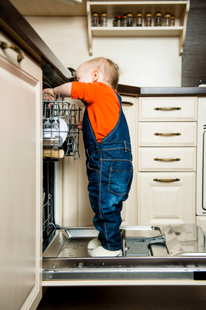 emptying: Cute baby standing on dishwasher in kitchen and helps it unload Stock Photo