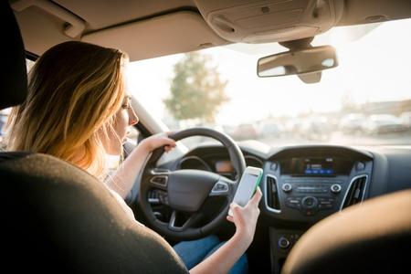 Mujer joven que mira a su teléfono inteligente mientras conduce el coche - vista posterior, sol brilla a través de la ventana frontal