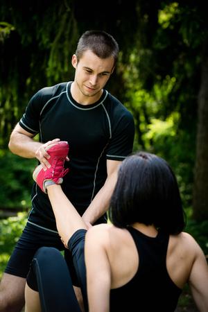 convulsion: El hombre ayuda a la mujer con el espasmo muscular - se extiende la pierna