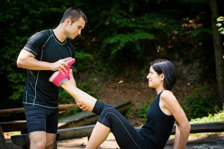 convulsion: El hombre estira las piernas womans - espasmo muscular después del entrenamiento deportivo