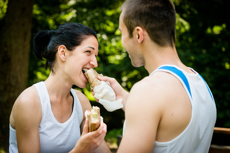 feed: Young couple eating after sport training outdoor in nature - man feeds woman Stock Photo