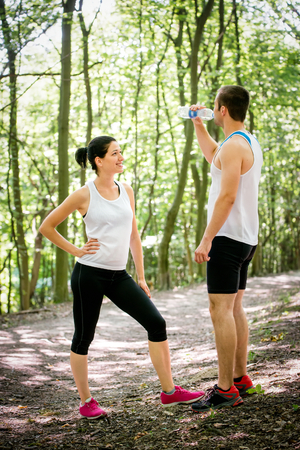 gasp: Young couple relaxing after jogging in nature, man drinking water Stock Photo