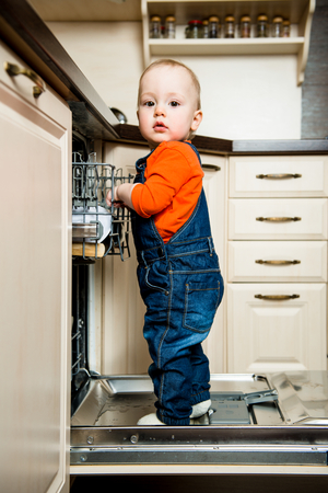 babies hands: Cute baby standing on dishwasher in kitchen and helps it unload Stock Photo