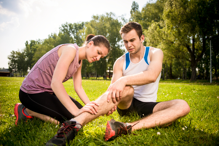 injured woman: Woman is helping to young man with injured leg from sport activity Stock Photo