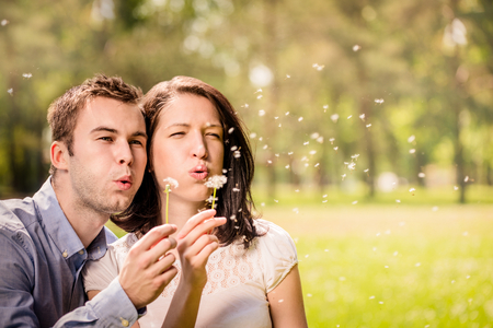 couple nature: Young happy couple blowing together dandelions, outdoor in nature