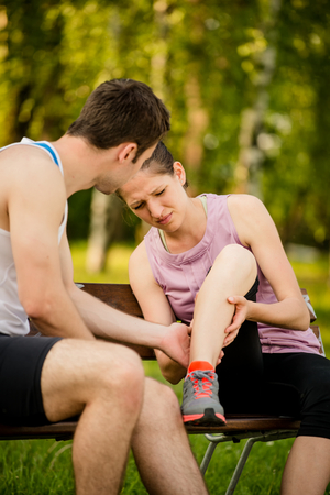 calf pain: Man helps to woman who injured her leg when jogging