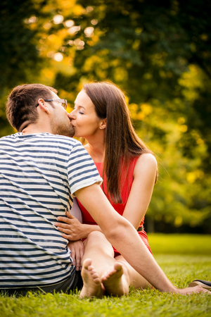 femme romantique: Jeune couple souriant assis et embrasser sur l'herbe - femme aux pieds nus Banque d'images
