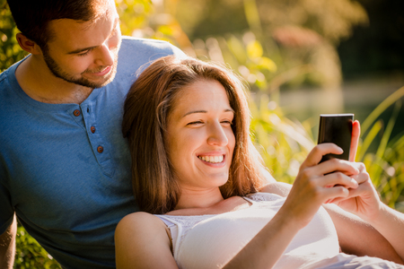 dating: Couple dating in sunny summer nature, woman looking to mobile phone