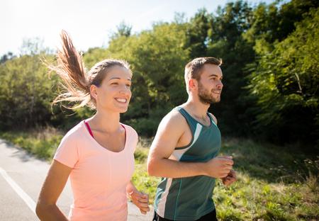 corriendo: Primer plano de la sonrisa de los amigos que se ejecutan juntos en la naturaleza soleado de verano