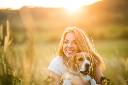 Teen girl having fun with beagle dog outdoor in nature  at summer sunset