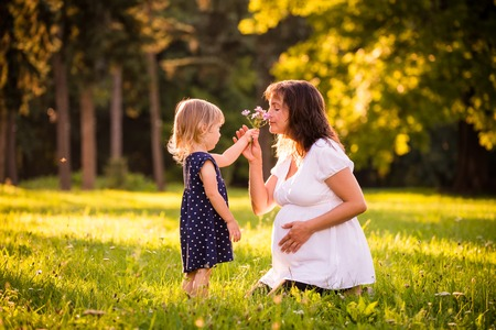 Child giving her her pregnant mother flower outdoor in sunny nature