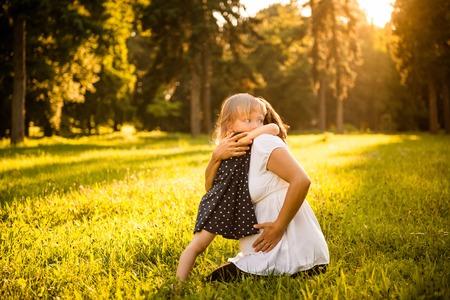 mama e hija: Niño que abraza a su madre embarazada al aire libre en la naturaleza soleada