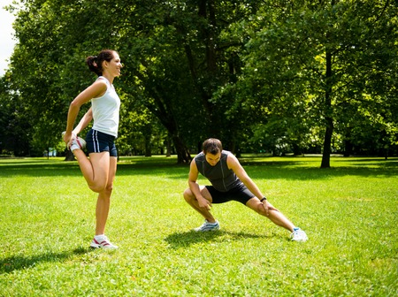 sports training: Young couple exercising and stretching muscles before sport activity - outdoor in nature Stock Photo