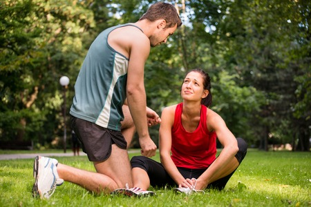 injured woman: Sport injury - young fitness woman holding her ankle  with pain, man is helping Stock Photo