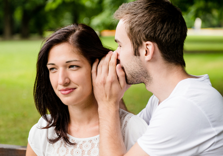 tenager: Young man whispering to woman (girlfriend) - outdoor lifestyle photo