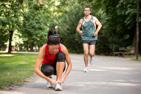 shoelace: Young sport woman tying shoelace, man in behind is jogging Stock Photo