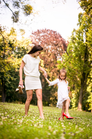 Daughter wearing big red high-heeled shoes of her mother  in nature Stock Photo - 52577751