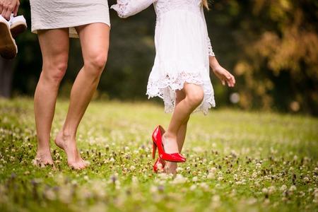 on high: Hija que lleva grandes zapatos de tacón alto de color rojo de su madre en la naturaleza Foto de archivo