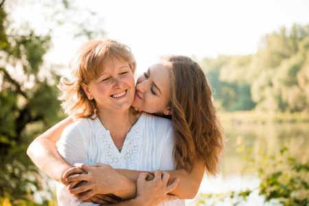 mother: Mature mother hugging with her teen daughter outdoor in nature on sunny day
