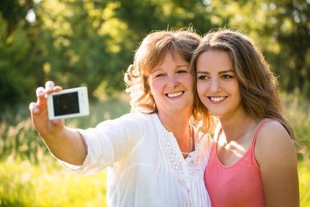 madre e hija adolescente: Hija adolescente y su madre senior están tomando la foto selfie con el teléfono móvil