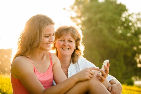 smiling teenagers: Teenage girl showing her mother photos on mobile phone outdoor in nature with setting sun in background Stock Photo
