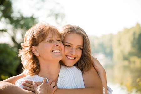 Mature mother hugging with her teen daughter outdoor in nature on sunny day
