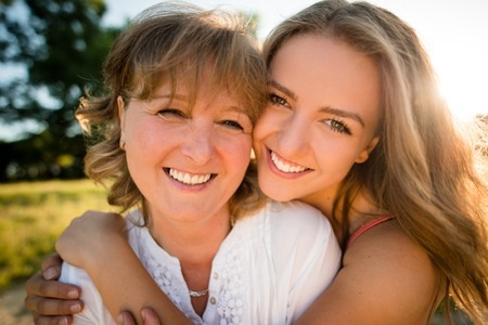 Portrait of mother and her teenage daughter outdoor in nature with setting sun in background Banque d'images