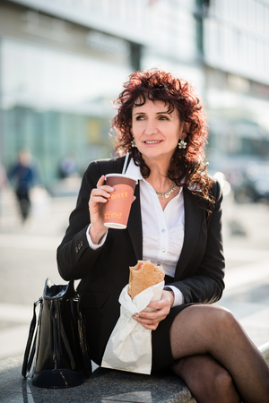 mature women: Senior business woman having quick meal in street - drinking take-away coffee and eating baguette Stock Photo