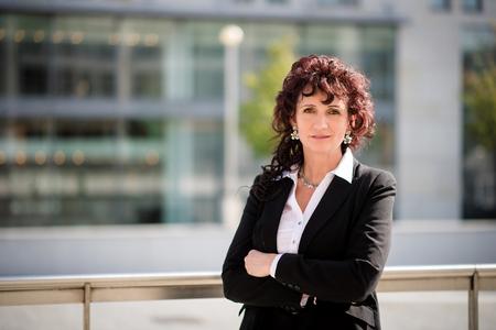 headshot: Portrait of confident senior business woman outdoor in street Stock Photo