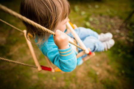 authentic: Child swinging on seesaw in backyard - above view