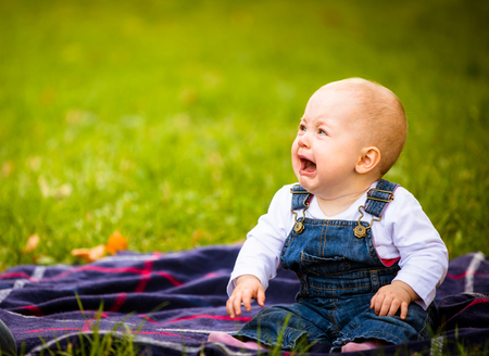 babby: Babby sitting on rug and crying - outdoor setting with copy space