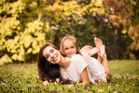bare foot girl: Beautiful happy mother lying down on grass with her girl - outdoor in nature